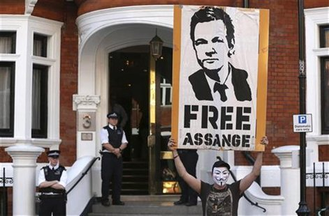 A protestor holds a poster of Wikileaks founder Julian Assange outside Ecuador's embassy in London August 17, 2012. REUTERS/Neil Hall