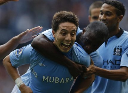 Manchester City's Samir Nasri (L) celebrates with Yaya Toure after scoring his side's third goal during their English Premier League soccer