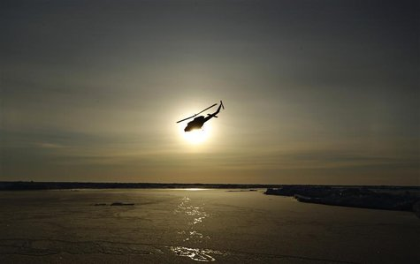 A helicopter flies over Arctic ice towards the Applied Physics Laboratory Ice Station (APLS) during an exercise near the 2011 APLS camp nort