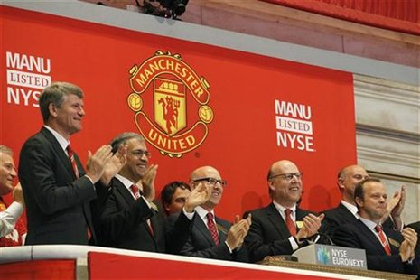 Manchester United executives and owners Joel (3rd L) and Avram Glazer (2nd R) ring the opening bell in celebration of Manchester United Ltd