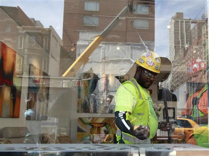 Construction workers clean up an art gallery that was damaged following a blast at a subway construction site in New York August 21, 2012. R