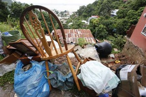 Furniture and other belongings are stacked outside as a resident prepares to move out of a house damaged by a mudslide caused by the passing of Tropical Storm Isaac at Upper Neckles Drive, Carenage August 23, 2012. REUTERS/Andrea De Silva