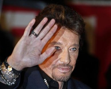 French singer Johnny Hallyday waves as he arrives at the Cannes festival palace to attend the NRJ Music Awards in Cannes January 28,2012. RE