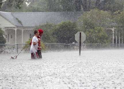 Residents of Mandeville walk through a flooded street as Hurricane Isaac passes through Mandeville, Louisiana, August 30, 2012. REUTERS/Jona