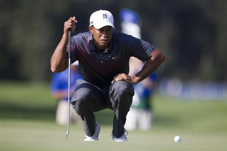 Tiger Woods of the U.S. lines up a putt at the 13th hole during the first round of the Deutsche Bank Championship golf tournament in Norton,