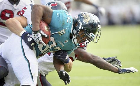 Running back Maurice Jones-Drew of the Jacksonville Jaguars (R) is tackled by the Houston Texans defense during the second half of their NFL