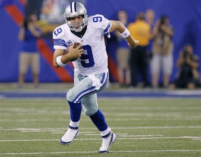 Dallas Cowboys quarterback Tony Romo (9) runs with the ball against the New York Giants during their NFL football game in East Rutherford, N