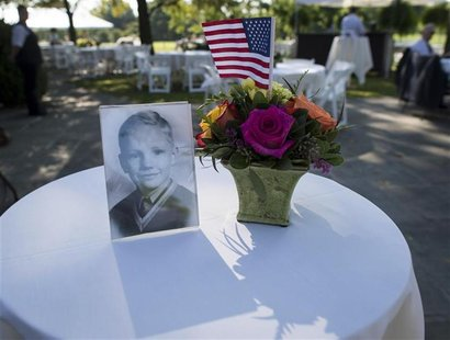 A photograph of Neil Armstrong as a young man is displayed on a table during a memorial service celebrating the life of Armstrong at the Cam