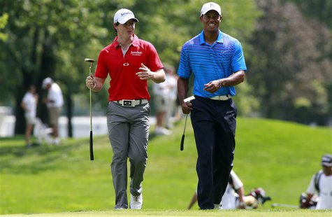 Rory McIlroy (L) of Northern Ireland talks with Tiger Woods of the U.S. as they approach the first green during round one of the BMW Champio