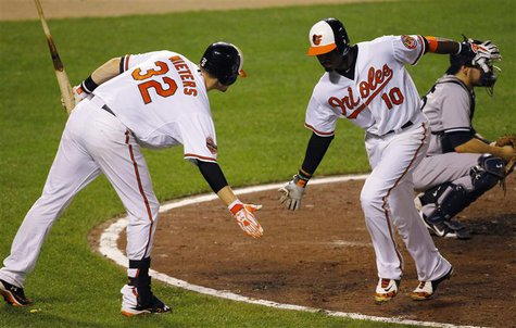Baltimore Orioles hitter Adam Jones (R) is welcomed by teammate Matt Wieters after his go-ahead, solo home run against the New York Yankees