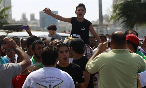 Syrian protesters and Muslim Brotherhood's supporters shout slogans against Syria's President Bashar al-Assad, Iran and Hazeb Allah in the M
