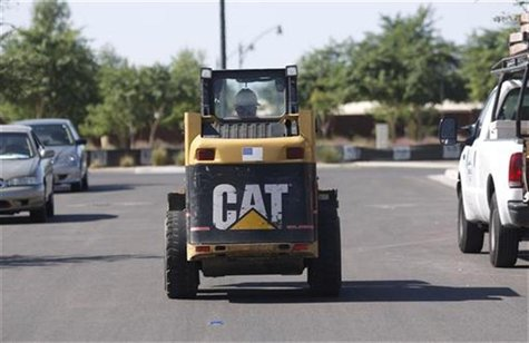 A worker drives a Caterpillar tractor near a construction site in Gilbert, Arizona October 20, 2009. REUTERS/Joshua Lott