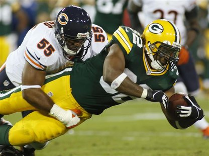 Green Bay Packers running back Cedric Benson (R) is tackled by Chicago Bears linebacker Lance Briggs in the first half during their NFL foot