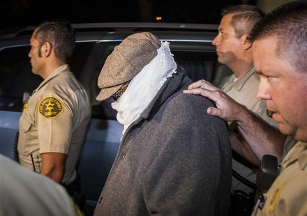 An unidentified person (C) is escorted out of Nakoula Basseley Nakoula's home by Los Angeles County Sheriff's officers in Cerritos, Californ