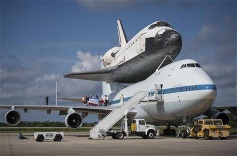 Workers pose for a photograph on the wing of NASA's Shuttle Carrier Aircraft, (SCA) with the space shuttle Endeavour mated on top, at the Ke