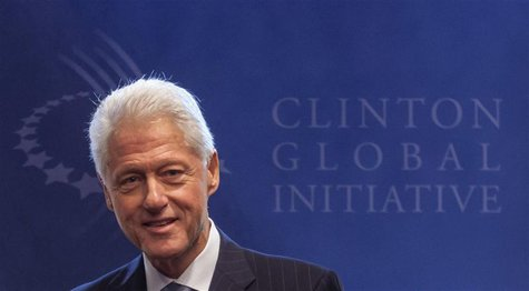 Former U.S. President Bill Clinton stands in front of the logo of the Clinton Global Initiative 2012 (CGI) during the first day of the CGI i