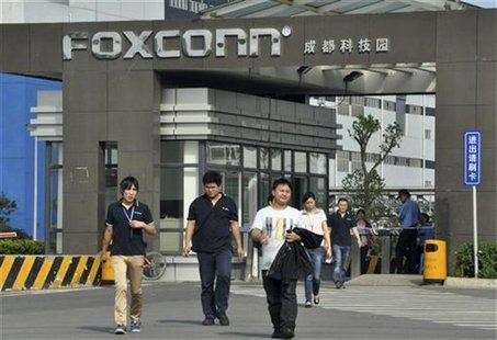 Workers walk out of the entrance to a Foxconn factory in Chengdu, Sichuan province July 4, 2012. REUTERS/Stringer