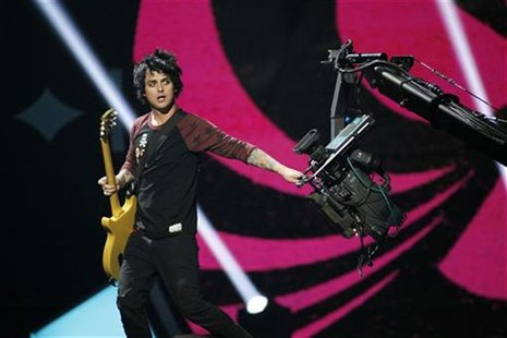 Green Day lead vocalist and guitarist Billie Joe Armstrong grabs a camera during the 2012 iHeart Radio Music Festival at the MGM Grand Garde