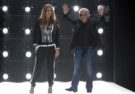 Italian designer Roberto Cavalli and his wife Eva acknowledge applause on the catwalk at the end of his Spring/Summer 2013 collection at Mil