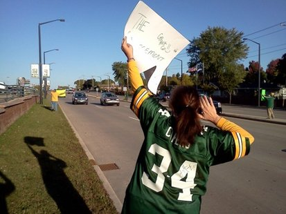 Packers fan Tamie Vertz holds a sign along Lombardi Avenue in front of Lambeau Field. (courtesy of FOX 11).