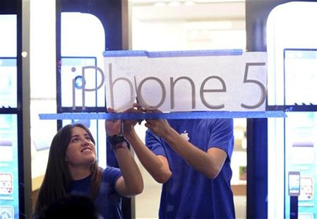 Apple employees hang an iPhone 5 sign at one of the company's retail locations shortly before sales began in San Francisco, California, Sept