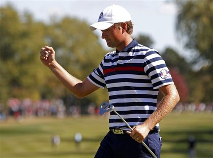 U.S. golfer Webb Simpson celebrates sinking a birdie putt to win the 10th hole during the 39th Ryder Cup singles golf matches at the Medinah