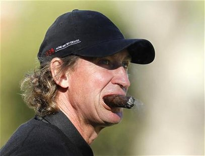 Hockey great Wayne Gretzky smokes a cigar as he plays in a pro-am event at the Chevron World Challenge golf tournament in Thousand Oaks, Cal