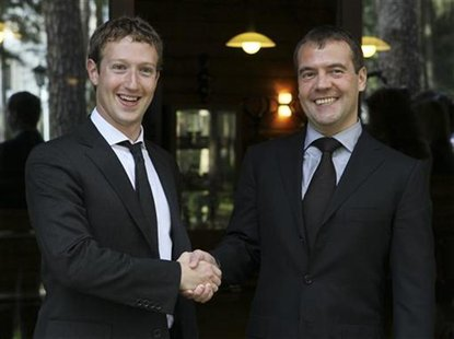 Russian Prime Minister Dmitry Medvedev (R) shakes hands with Facebook CEO Mark Zuckerberg during their meeting at the Gorki residence outsid