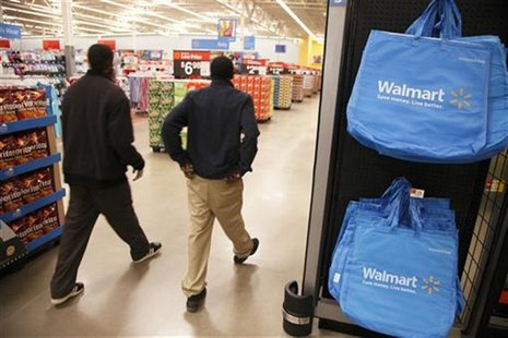 Workers walk through a new Wal-Mart store in Chicago, January 24, 2012. The store will open on January 25, and it will be Wal-Mart's largest