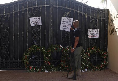 A Libyan government militia guarding the main entrance of the U.S. consulate that was attacked last week, fixes a note written by Libyans ag