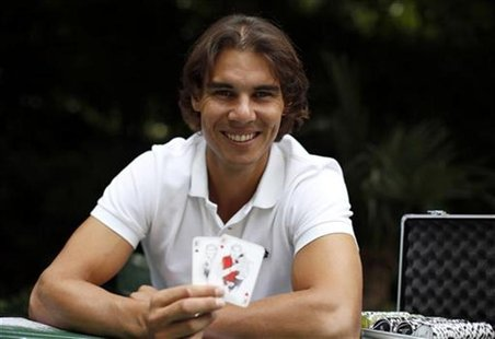 Spanish tennis player Rafael Nadal poses with playing cards depicting some of his 11 Grand Slam victories after an interview with Reuters in