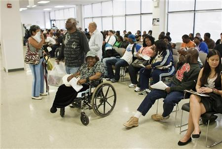 Larry Johnson (C) stands next his mother Ethel, 87, sitting in her wheelchair as they wait to get a voter ID card inside a Pennsylvania Department of Transportation office in Philadelphia