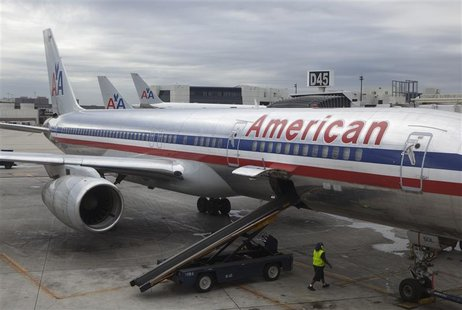 A worker walks underneath an American Airlines airplane at Miami International airport in Miami, Florida in this November 29, 2011, file pho