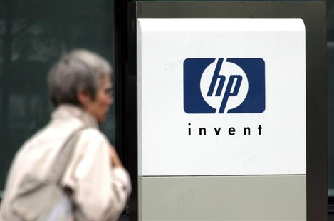 A woman walks past the Hewlett Packard logo at its French headquarters in Issy le Moulineaux, western Paris, in this September 16, 2005 file