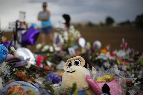 A stuffed animal peeks out from a mound of others at the marker for 6-year-old victim Veronica Moser-Sullivan at a memorial for the theater-