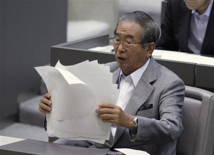 Tokyo Governor Shintaro Ishihara organises his documents after delivering a policy speech about the territorial dispute over the uninhabited