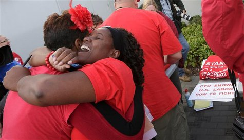 Jacqueline Robinson (R) hugs another member of the Chicago Teachers Union as they celebrate the end of their strike in Chicago September 18,