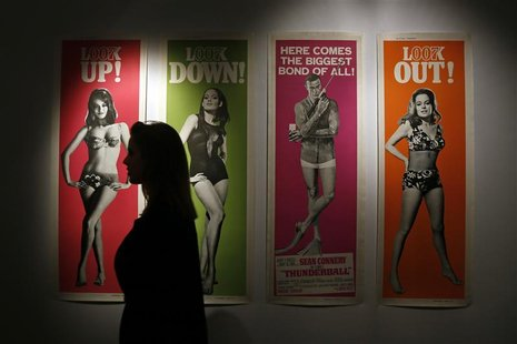 "A worker walks past a complete set of original cinema door panel posters from the film ""Thunderball"", during a media preview of ""50 Years of"