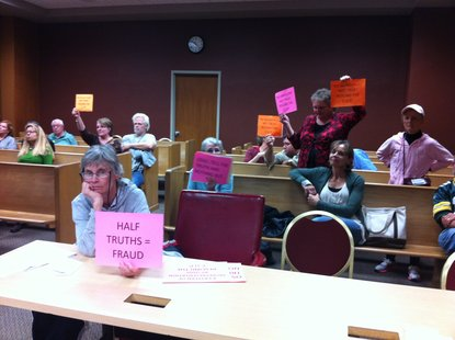 The remaining opposition to the facility hold signs up as they realize the committee was going to vote to keep the of the permit in place Wednesday night.