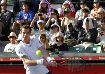 Andy Murray of Britain returns a shot to Stanislas Wawrinka of Switzerland in front of spectators shielding from the sun during their men's