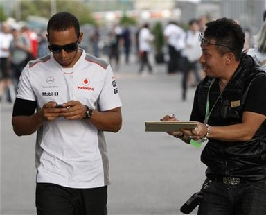 A fan asks McLaren Formula One driver Lewis Hamilton of Britain for an autograph as he walks in the paddock after the second practice sessio