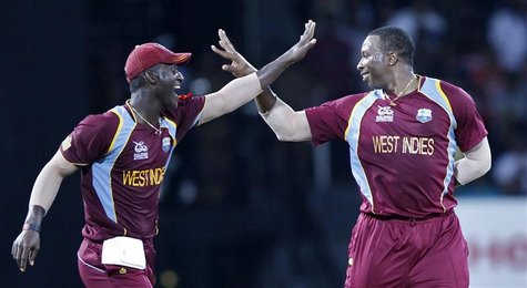 West Indies' Kieron Pollard (R) celebrates with his captain Darren Sammy after taking the wicket of Australia's Pat Cummins during their Twe