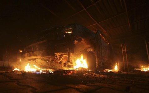 A burning car is seen at the U.S. Consulate in Benghazi during a protest by an armed group said to have been protesting a film being produce