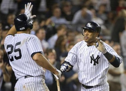 New York Yankees batter Robinson Cano celebrates with teammate Mark Teixeira (25) after he hit a two-run home run, his second of the game, a