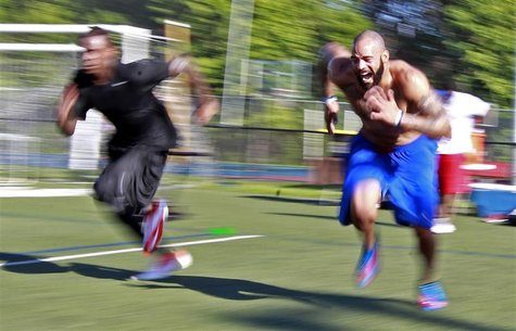 Jyles Tucker (R) and Legedu Naanee run sprints during workouts with other NFL hopefuls at the Bommarito Performance Systems facility in Nort
