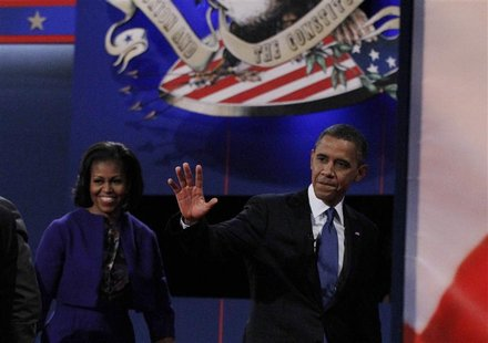 President Barack Obama waves as he and his wife Michelle depart the stage after the end of the first presidential debate against Republican