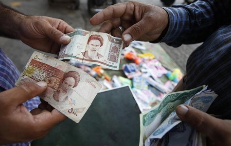 A customer changes Iraqi dinars to Iranian rials at a money changer in Baghdad, October 4, 2012. REUTERS/Thaier al-Sudani