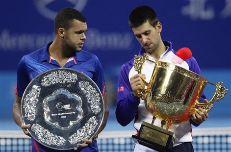 Serbia's Novak Djokovic (R) stands with France's Jo-Wilfried Tsonga with their trophies after winning the men's singles final at the China O