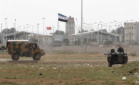 Turkish troops take their position at the Akcakale border gate in southern Sanliurfa province October 7, 2012, as a Syrian Independence flag