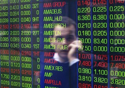 An office worker talks on his phone as he looks the stock board at the Australian Securities Exchange (ASX) building in central Sydney June